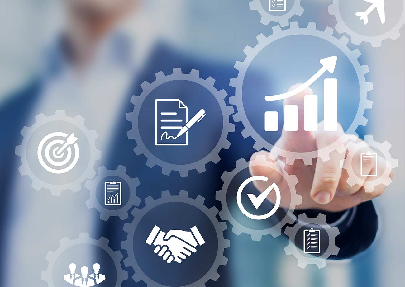 Man pointing to business symbols representing goals and growth.